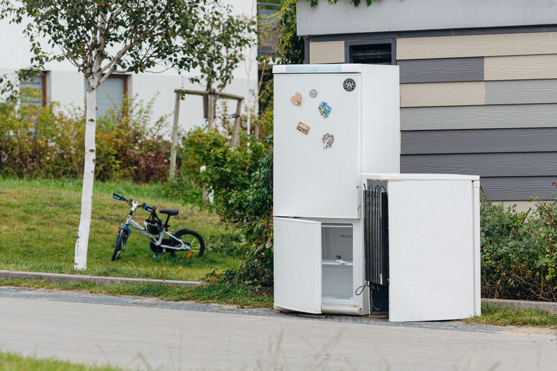 Lodówka i lodówko-zamrażarka stoją na ulicy przy altanie śmietnikowej. Po lewej trawnik i młoda brzózka