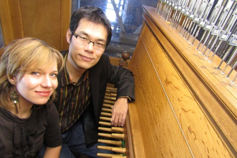 Twarz kobiety Polki z lewej strony, twarz mężczyzny Japończyka - nieco na prawo od niej. Mężczyzna opiera lewą rękę na klawiaturze carillonu