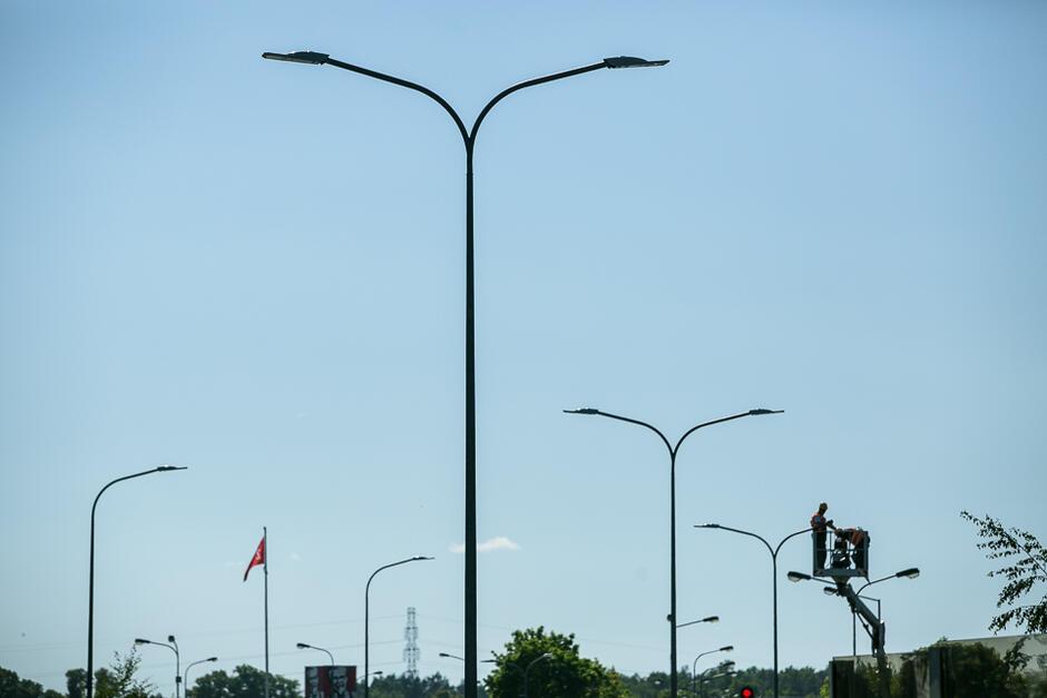 Na zdjęciu widoczni są dwaj pracownicy na podnośniku, którzy dokonują wymiany opraw oświetleniowych na jednym ze słupów latarni ulicznych.