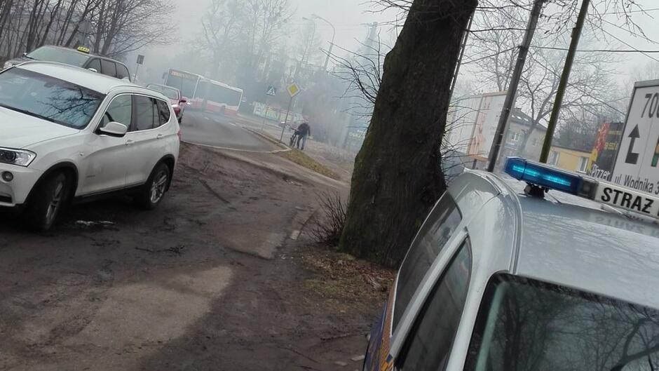 zadymiona ulica pień drzewa radiowóz samochody osobowe taksówka rowerzysta znaki drogowe autobus