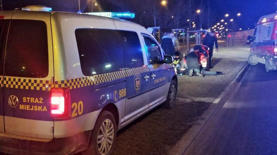 Radiowóz karetka pogotowia ludzie reanimują poszkodowanego ulica drzewa