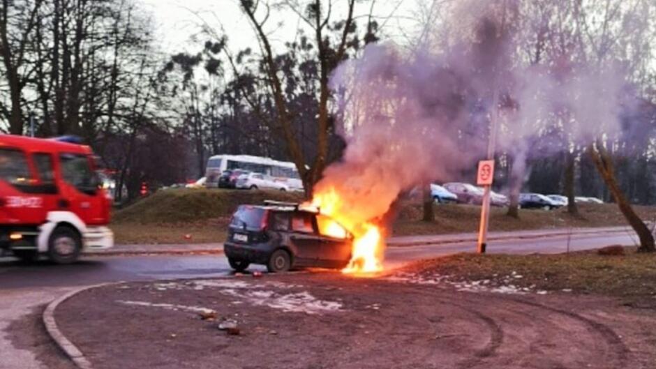 płonący samochód fiat Punto samochód Straży Pożarnej zaparkowane samochody ulica trawnik