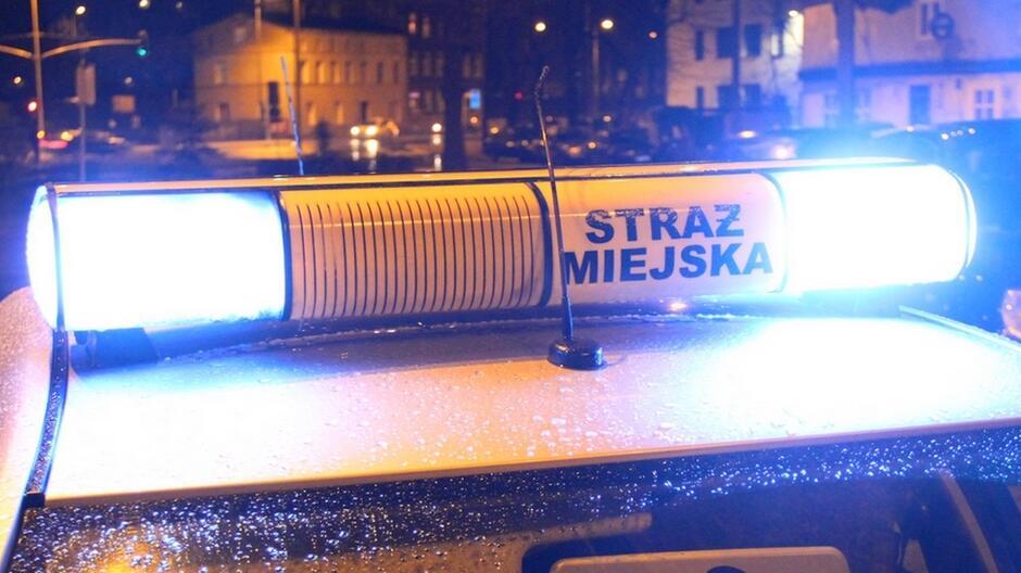 lampa sygnalizacyjno-ostrzegawcza z napisem straż miejska dach radiowozu sygnalizacja świetlna kamienice