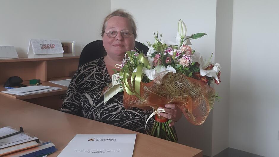 Pani Tatiana siedzi przy swoim biurku. W ręku trzyma bukiet kwiatów, który dostała na pożegnanie.