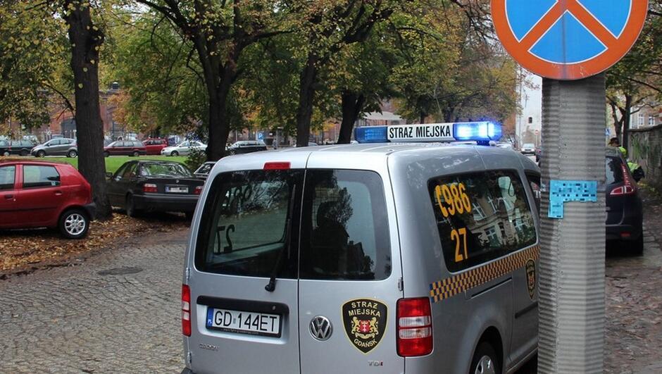 radiowóz zaparkowane samochody wybrukowana ulica plac Wałowy drzewa trawnik znak drogowy zakaz zatrzymywania strażnicy