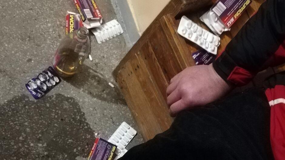 opakowania po tabletkach Ibuprom otwarta buteka wina rozrzucone na podłodze z lastryko fragment ławka fragment siedzącego mężczyzny