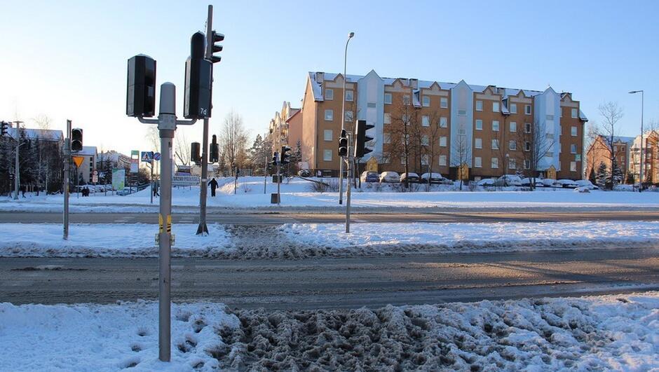 zaśnieżona ulica sygnalizacja drogowa bloki mieszkalne reklamy piesi znaki drogowe samochód drzewa