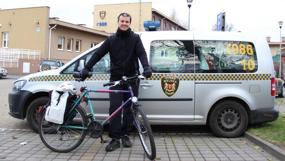 plac przed siedzibą Straży Miejskiej przy ulicy Elbląskiej rowerzysta z rowerem radiowozy samochody osobowe siedziba straży miejskiej