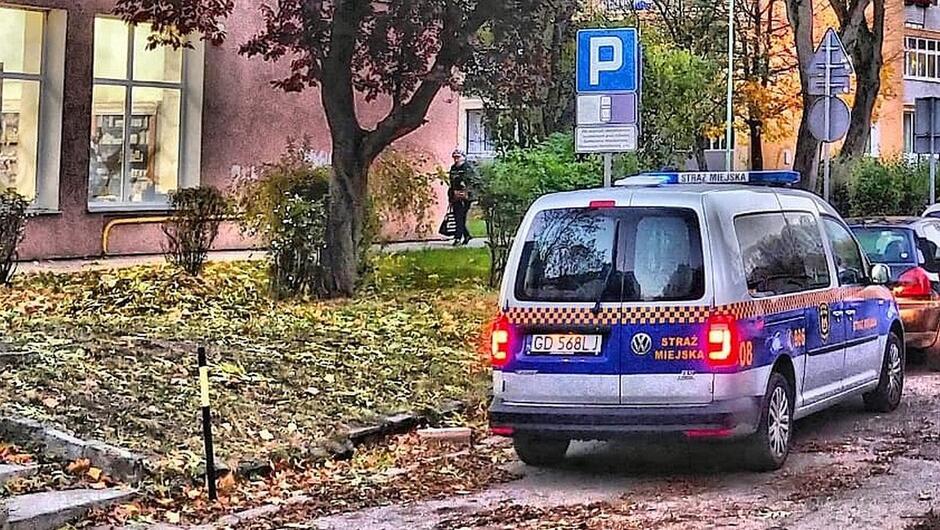 radiowóz zaparkowany samochód osobowy znaki drogowe drzewa sklep trawnik pokryty liśćmi blok mieszkalny