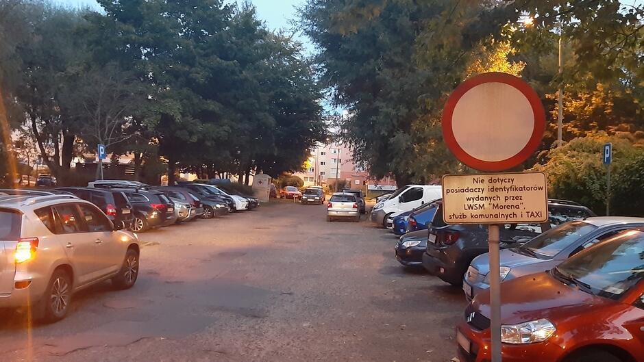 ulica Matuszewskiego parking zaparkowane samochody znak drogowy zakaz ruchu nie dotyczy posiadaczy idnetyfikatórów LWSM Morena bloki drzewa