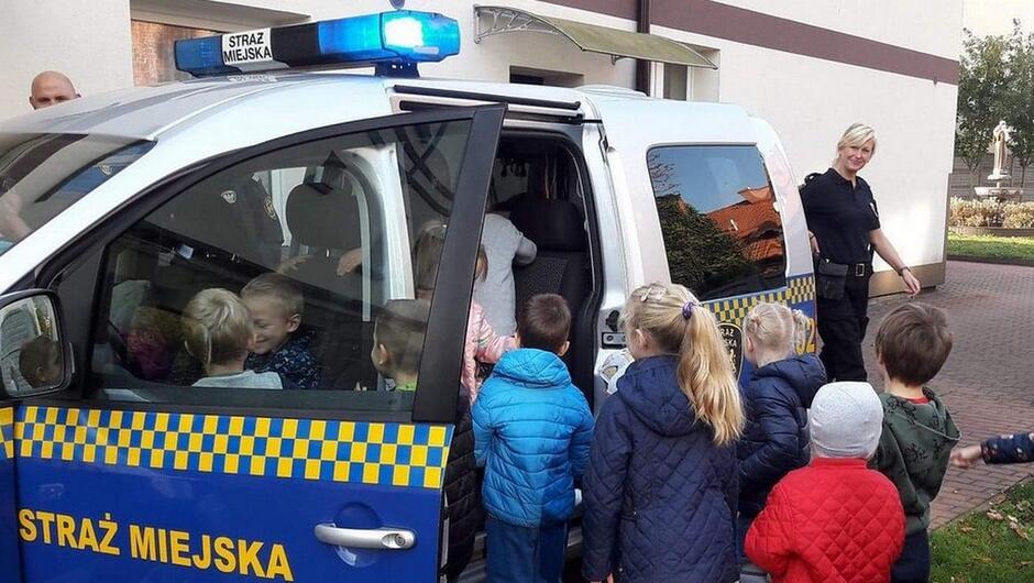 dzieci wchodzą do radiowozu strażnicy budynek wybrukowany plac fontanna