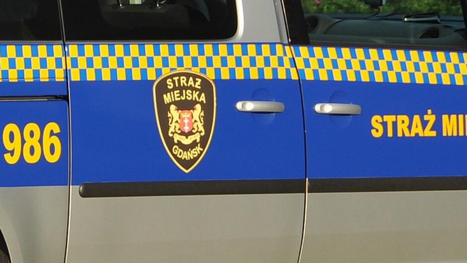 bok radiowozu szachownica straży miejskiej numer zgłoszeniowy 986 emblemat straży miejskiej
