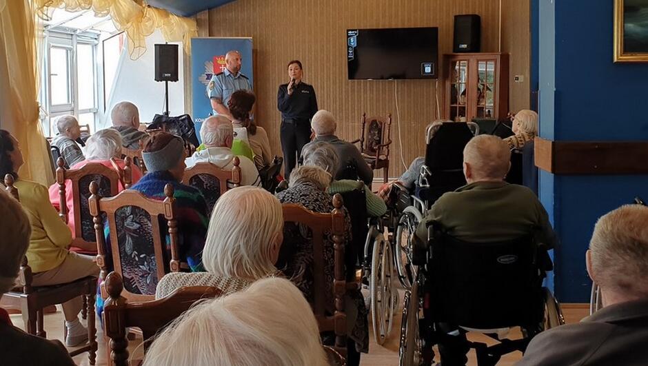 grupa seniorów, część siedzi na wózkach inwalidzkich krzesła sala strażnik policjantka baner Policja telewizor obraz firnaki w oknach szafka