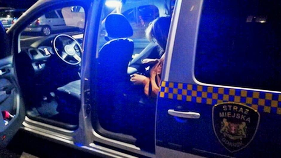 otwarty radiowóz kobieta siedząca na tylnym siedzieniu zaparkowane samochody