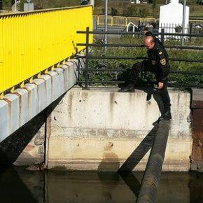 strażnik pochylony nad Kanałem Raduni żółta barierka na mostku ulica ołtarzyk przy drodze