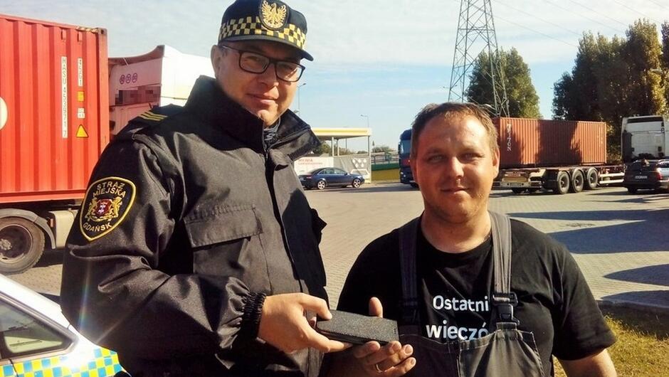strażnik przekazuje smartfon właścicielowi parking myjnia samochody TIR linia wysokiego napięcia drzewa