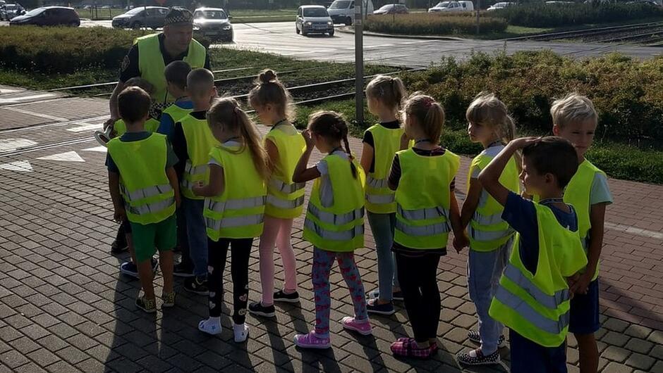 dzieci w kamizelkach odblaskowych strażnik torowisko samochody ulica chodnik żywopłot