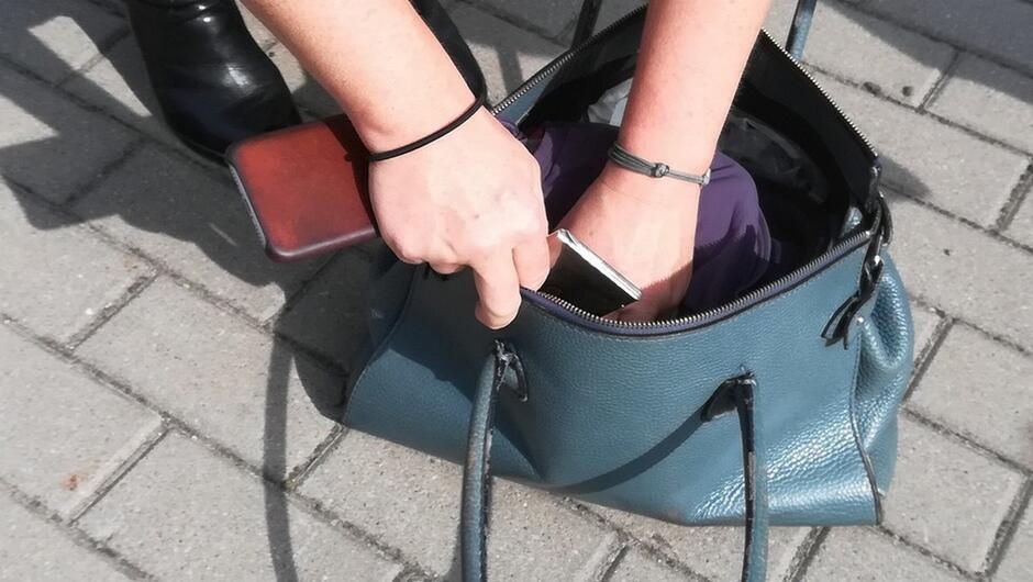 Damska torebka telefon komórkowy fragment chodnika wyłożony kostką brukową damskie dłonie włożone do torebki