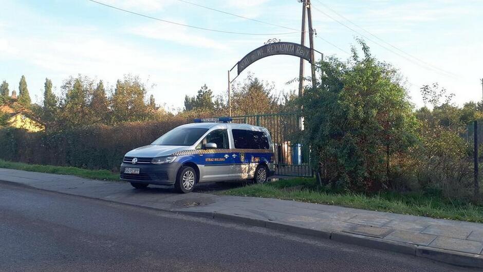 radiowóz ulica wjazd na Ogródki Działkowe dom zarośla drzewa