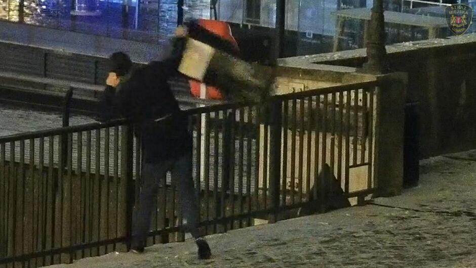 Zielony Most meżczyzna przerzuca kosz na śmieci ponad barierką promenada fragment budynku