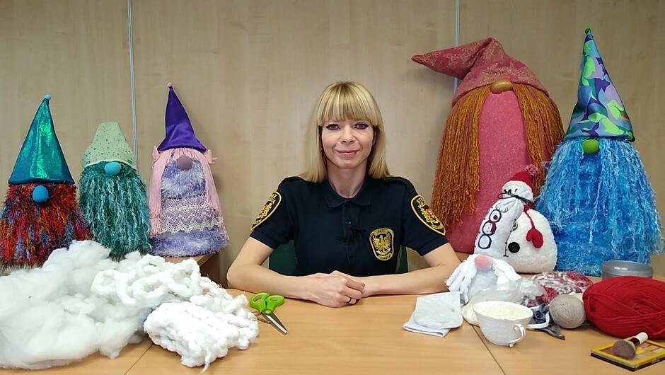 strażniczka miejska siedzi przy biurku wkoło ustawione kolorowe skrzaty różnej wielkości