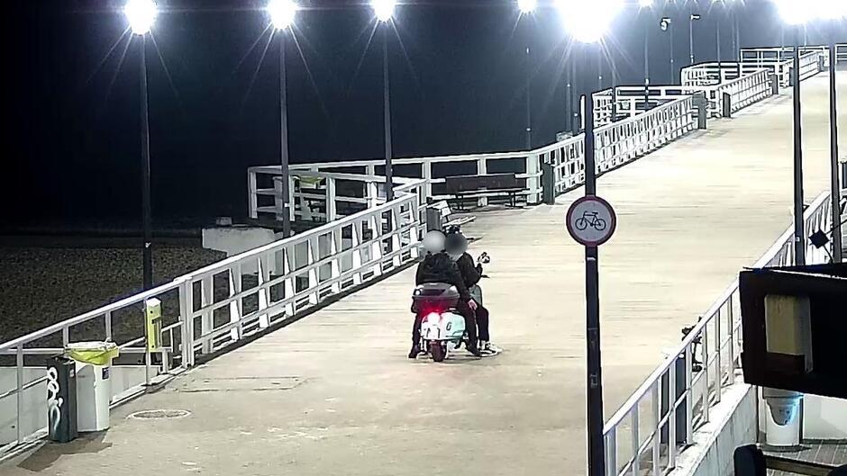 Mężczyźni jadący skuterem po molo w Brzeźnie_1