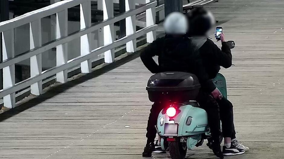 Mężczyźni jadący skuterem po molo w Brzeźnie_2
