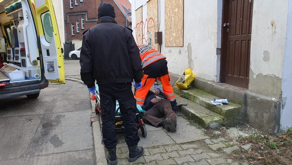 strażnik miejski ratownik medyczny udzielający pomocy wnętrze karetki budynki mieszkalne