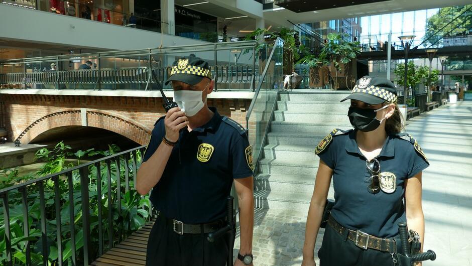 strażnik oraz strażniczka w patrolu w centrum handlowym