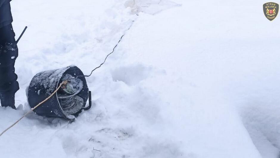 wiadro na śniegu z przedłużaczem elektrycznym fragment strażnika