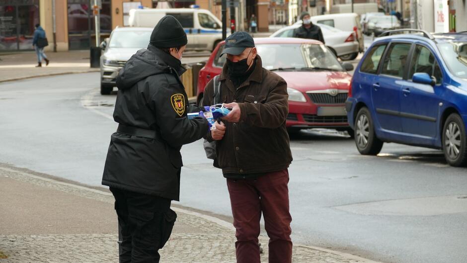 strażniczka daje maseczki mężczyżnie na ulicy przechodnie samochody budynki.JPG