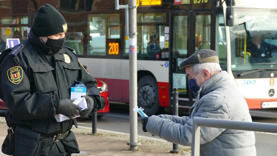 strażnik wręcza maseczki starszemu mężczyznie autobus linii 200.JPG