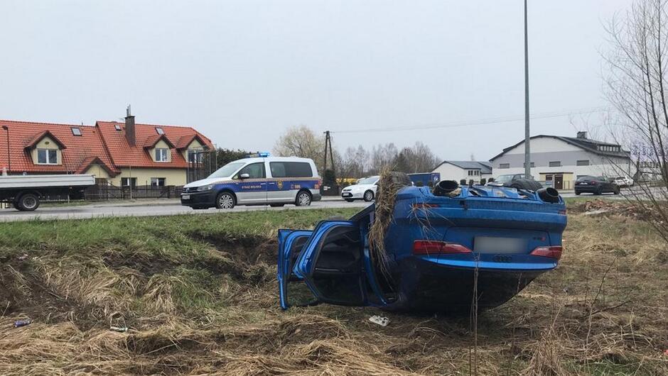 Przewrócony samochód i stojący na jezdni radiowóz straży miejskiej.