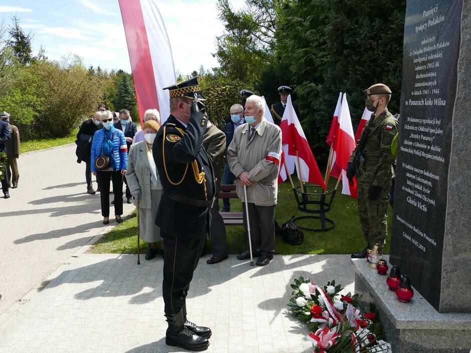 strażnik oddaje hołd pod pomnikiem Ofiar Ponar zaproszeni goście flagi Polski kwiaty.JPG