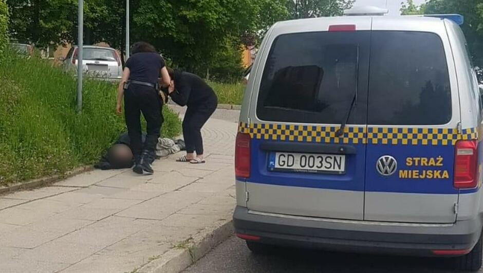Radiowóz strażniczka mężczyna leżacy na chodniku kobieta
