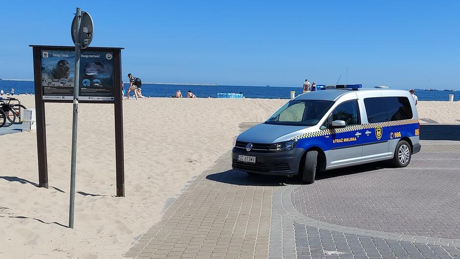 Radiowóz na deptaku przy plaży. rowery morze