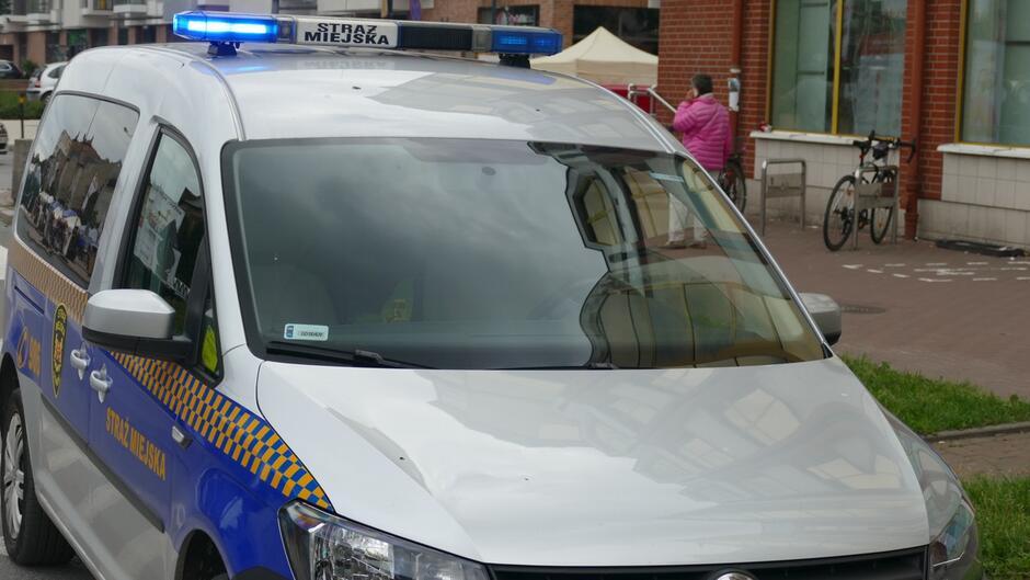 radiowóz kobieta z telefonem rower budynki.JPG