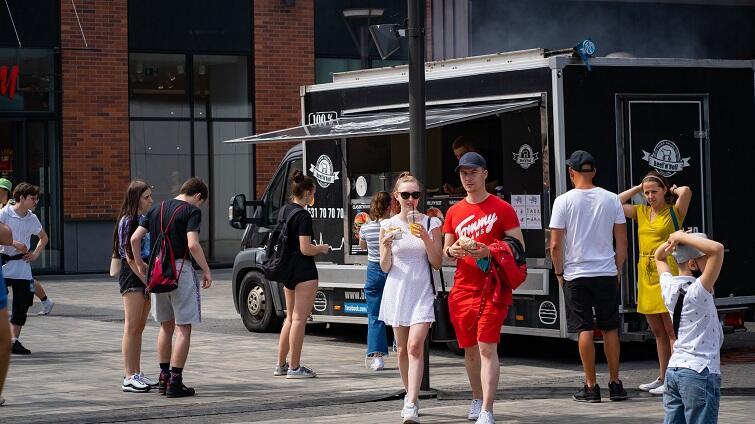 Zdjęcie przedstawia ludzi spacerujących w słonecznej pogodzie wśród foodtrucków